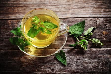 나무 배경에 유리 컵에 녹색 melissa 허브 차 스톡 콘텐츠