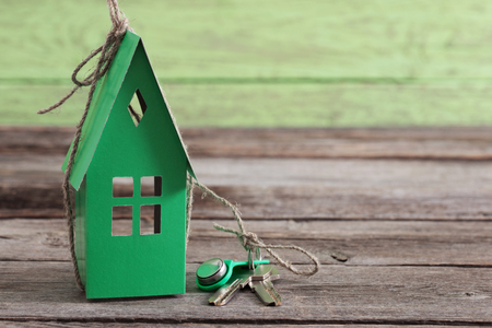 paper house on green wooden background Stock Photo