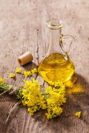 rapeseed oil (canola) and rape flowers on wooden table Standard-Bild