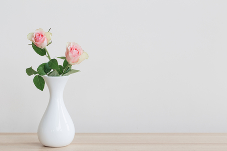 two pink roses in vase on white background