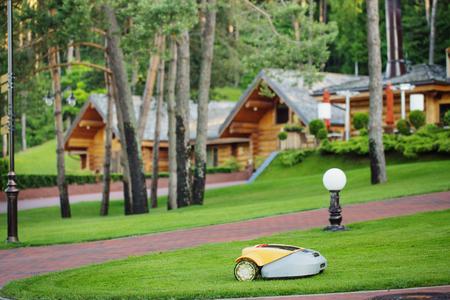 배경 목조 주택에 로봇 잔디 깎는 기계