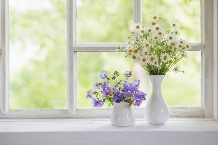 flowers in vases on windowsill