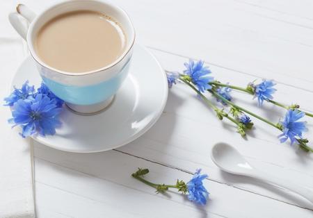 흰색 나무 테이블에 컵에서 치커리에서 마셔.