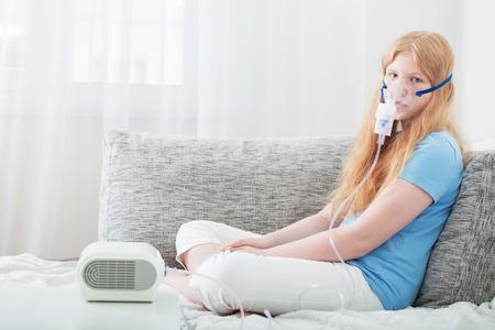 teenager girl doing inhalation indoor Foto de archivo