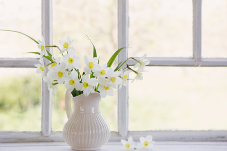 daffodils in jug on windowsill 免版税图像