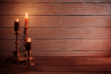 burning  candles in vintage  candlestick on wooden background