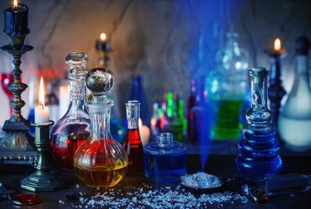 elixir: Poción mágica, libros antiguos y velas sobre fondo oscuro