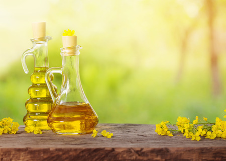 rapeseed oil (canola) and rape flowers on wooden table Stock Photo