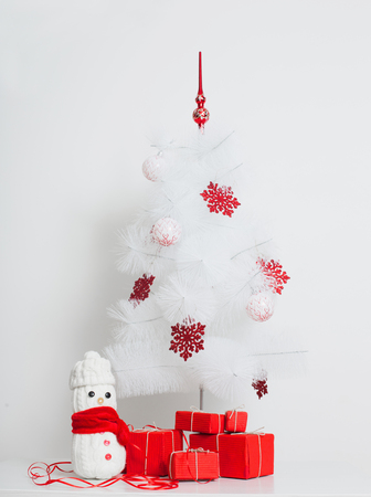 snowmen decoration by the Christmas tree with red gift box