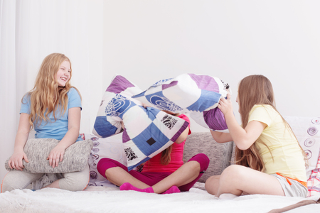 teenage girls  having fun and fighting with pillows Stock Photo