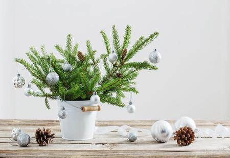 Christmas fir in bucket on old wooden table Foto de archivo