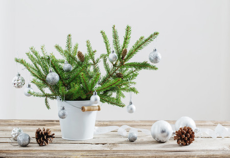 Christmas fir in bucket on old wooden table 免版税图像