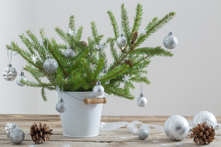 Christmas fir in bucket on old wooden table Stock Photo