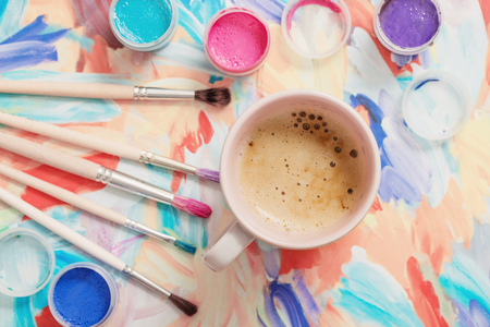 paints, brushes and cup of coffee on paper
