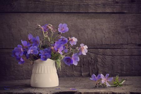 Flores azules en viejo fondo de madera Foto de archivo - 93134646