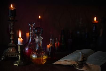 Magiczna mikstura, starożytne książki i świece na ciemnym tle