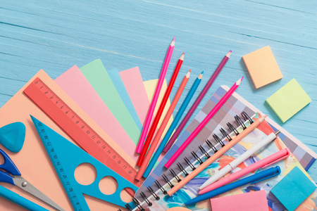 Collection of school supplies on blue wooden background