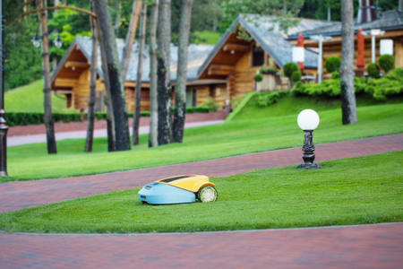 Robot lawn mower on background wooden houses Stockfoto