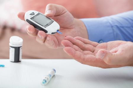 medycyna, cukrzyca, glikemia, opieka zdrowotna i koncepcja ludzi - zbliżenie męskiego palca z paskiem testowym