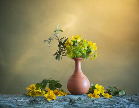 yellow flowers in vase on wooden table Standard-Bild