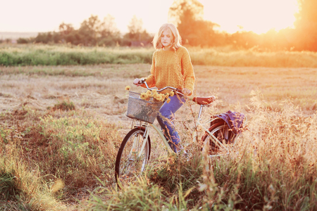 teenager girl on bike in summer field at sunset
