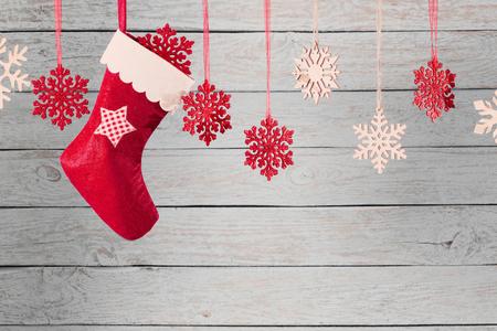 Calza di Natale che appende contro il fondo di legno