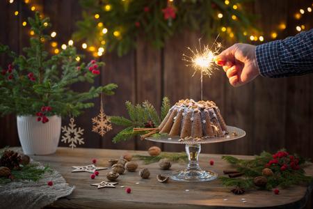 male hand sets fire to  sparkler on christmas cake Standard-Bild