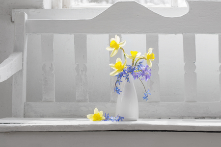 spring flowers in vase on white wooden bench 스톡 콘텐츠