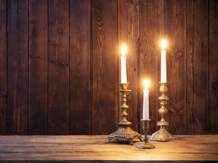 Vela encendida sobre fondo antiguo de madera oscura.