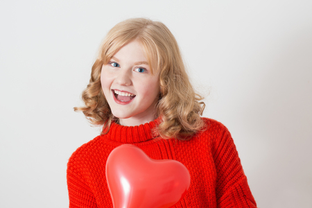 teen girl in red sweater with red balloons on white background