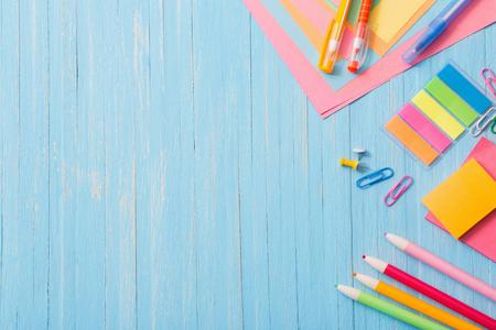 útiles escolares sobre fondo de madera azul