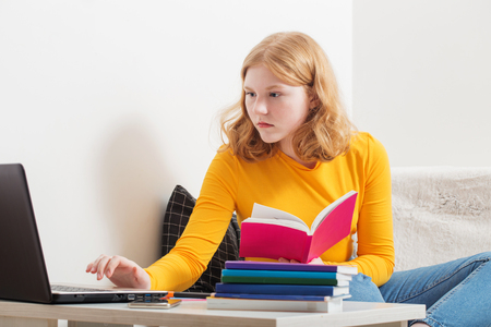 Teen girl studying and learning with  notebook at home.  Online education,e-learning.