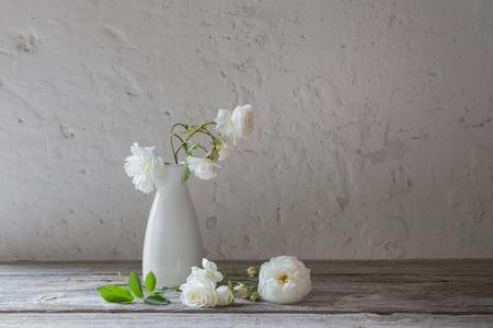 white roses in vase on old background