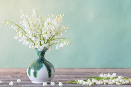 Maiglöckchen in Vase auf Holztisch