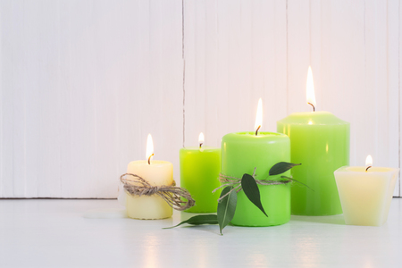 green burning candles on a white background