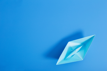paper boat on blue paper background Stockfoto