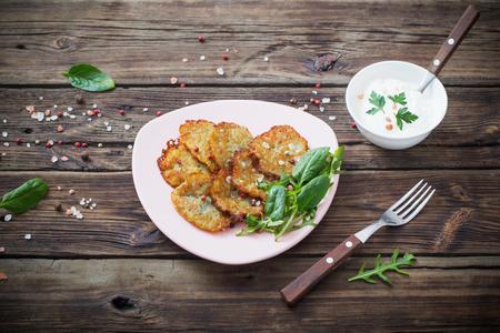 potato pancakes with sour cream on  wooden table