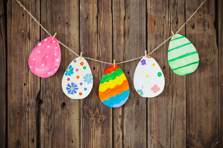Paper Easter painted eggs painted hang on clothespins on  background old wooden wall. 写真素材