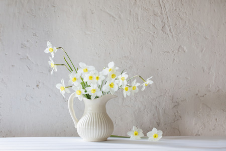 white daffodils in jug on white background