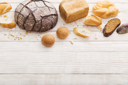 different types of bread on white wooden background Foto de archivo