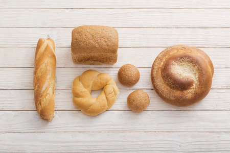different types of bread on white  wooden background