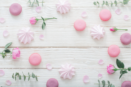 white wooden background with pink flowers, macaroons and leaves