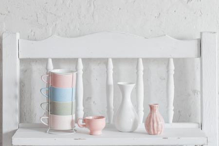 cups and vase on vintage white shelf Фото со стока