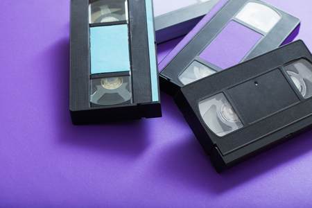 Video cassette on violet background. Retro concept
