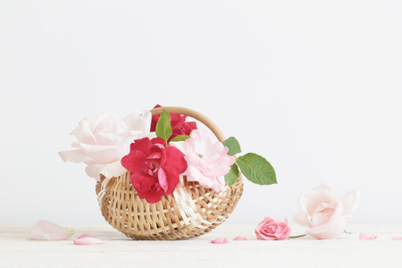 beautiful roses in basket on wooden table