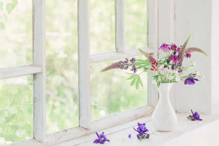 summer flowers in vase on white windowsill