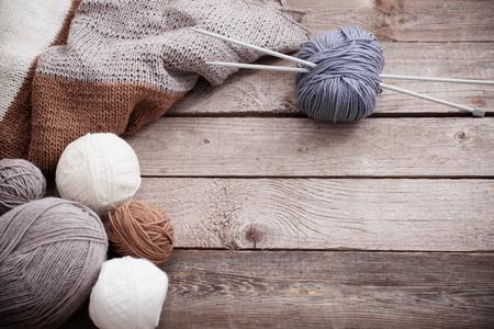 Ferri da maglia e maglieria su una superficie di legno