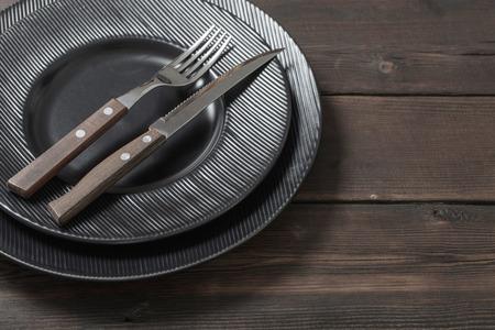 black plates on old  wooden background Standard-Bild - 124556052