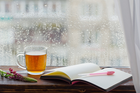 cup of tea on  background of  window with raindrops at sunset Banco de Imagens