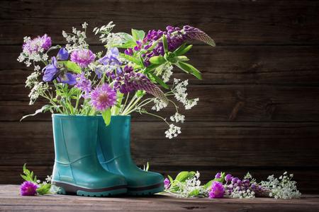 summer flowers in rubber boots on old dark wooden background Standard-Bild - 124556055
